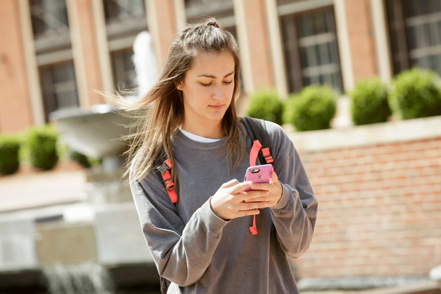 Student on phone in front of library fountain