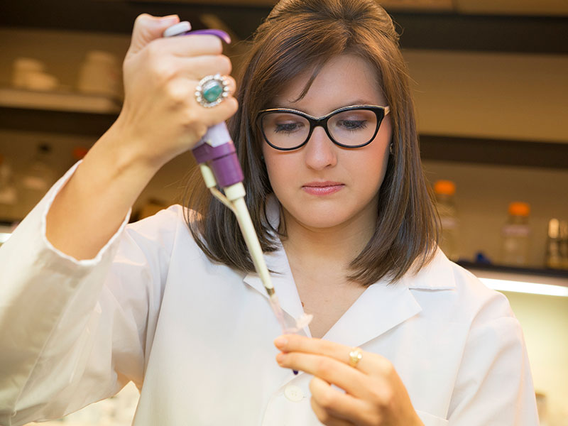A student fills a pipette in a lab.