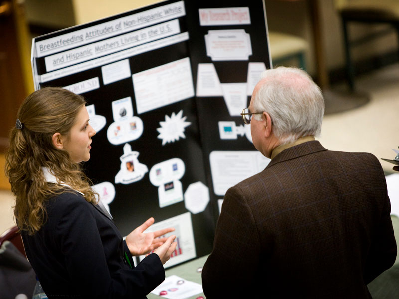 A student discusses their research findings with a faculty member.