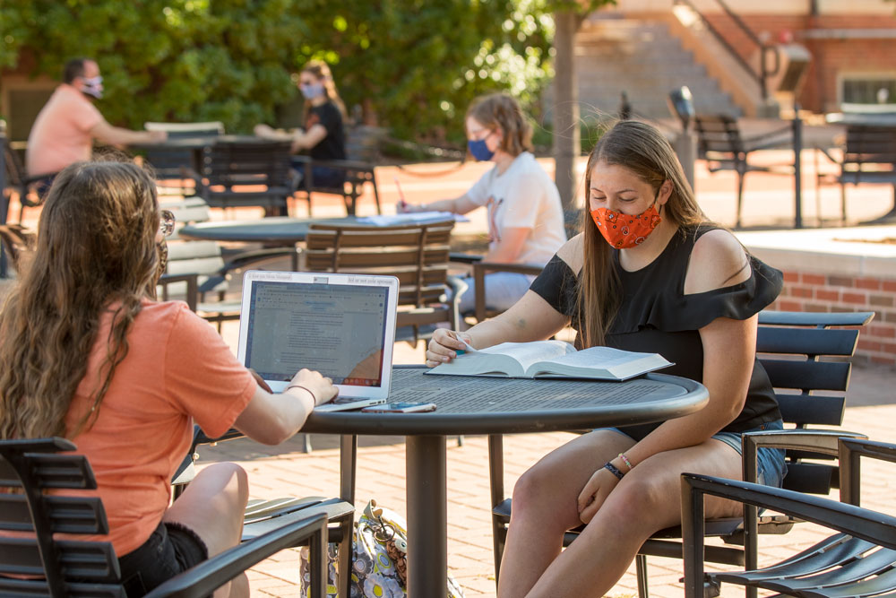 Students studying on the plaza with masks on