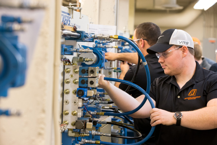 a mechanical engineering technology student moves large hoses on a panel of hook ups in a lab.