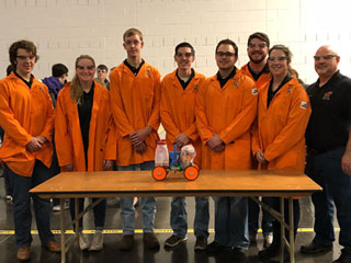 Class of chem students gather around for group photo in their bright orange medical coats