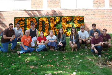 Landscape management students gather in front of homecoming sign decorated with flowers