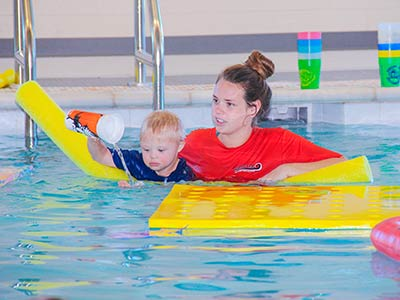 Student teaching her client in water therapy